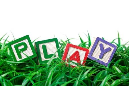 spell: Alphabet blocks forming PLAY on a patch of grass