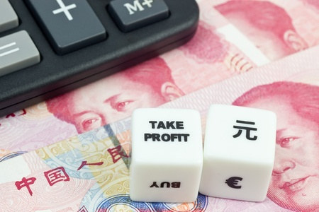 speculate: Chinese currency with calculator and dice showing TAKE PROFIT Stock Photo