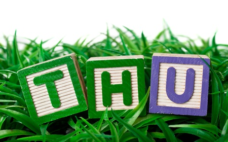 thursday: Alphabet blocks forming the letters THU on a patch of grass Stock Photo