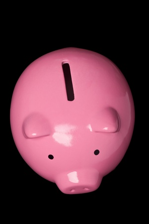 thrift box: Top view of a pink piggy bank isolated on black background