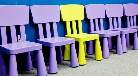 A yellow colored one in the middle of several purple colored chairs for children