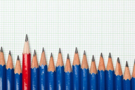 odd one out: Red pencil in the midst of a row of blue pencils on a piece of graph paper