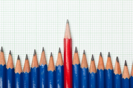 odd one out: Red pencil standing out from a row of blue pencils on a piece of graph paper Stock Photo