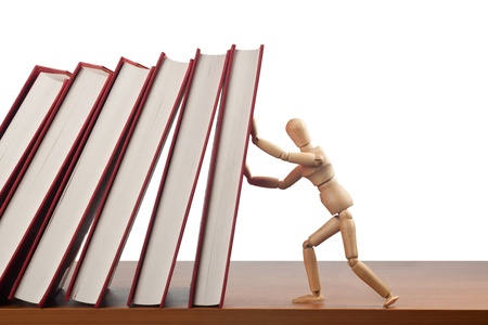 chain reaction: Figurine trying to stop a domino effect caused by the falling books  Stock Photo