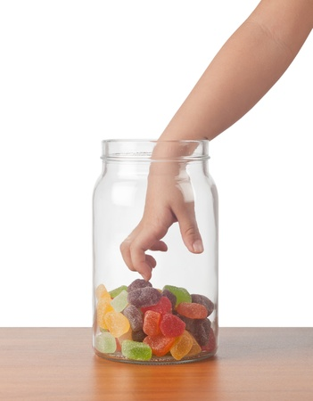 Childs hand reaching out to take candy from a jar