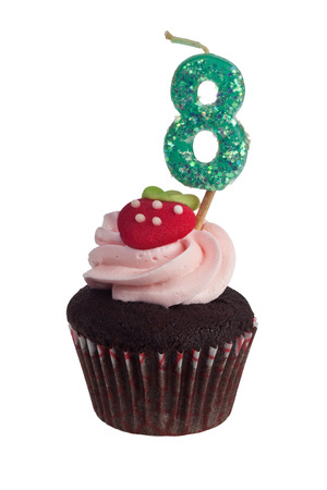 Mini cupcake with birthday candle for eight year old isolated on white background  Stock Photo