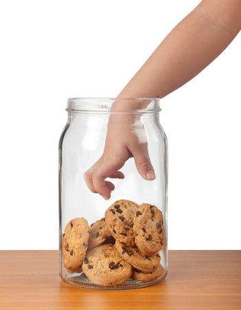 子供の手の壷からクッキーを取るに手を差し伸べる
