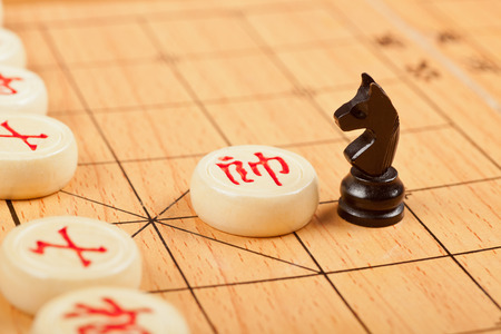 clash: Western chess piece on Chinese chess board