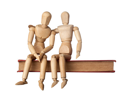 empathy: Consolation of a friend depicted by two figurines on a book isolated on white background