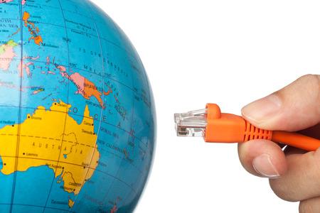 interlinked: Mano de conectar un cable de red para el mundo aislado en fondo blanco Foto de archivo