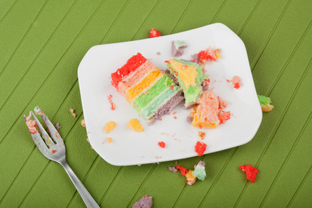 leftover: Messy leftover rainbow cake on a plate with crumbs around it  Stock Photo