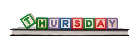 thursday: Alphabet blocks forming the word THURSDAY on a book isolated on white background