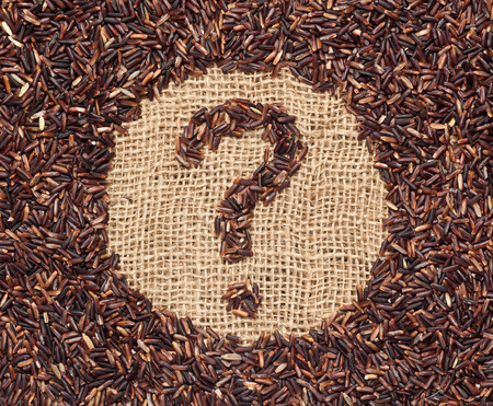 undetermined: Red rice forming a question mark on burlap fabric Stock Photo