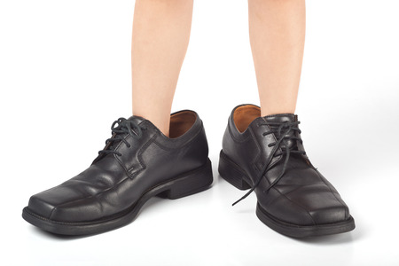 big shoes: Little kid wearing adult Stock Photo