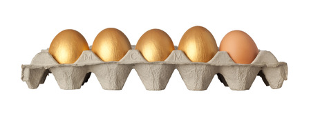 Four golden and one chicken eggs on a tray isolated on white background