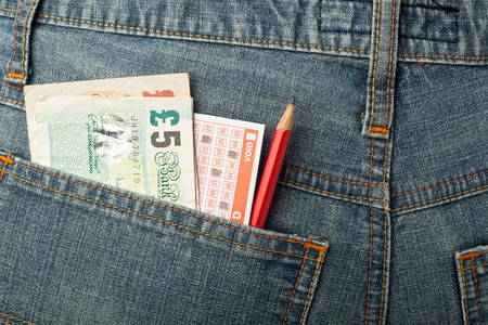 uk money: UK money and lottery betting slip in back pocket
