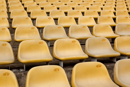 symmetrical: Rows of yellow symmetrical seats in a stadium