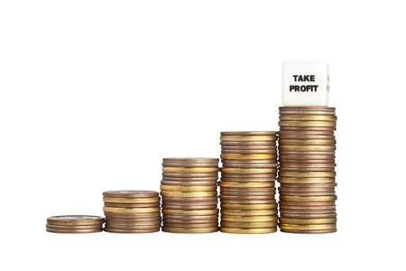 revenue: Stacks of increasing amount of coins with a Take Profit sign isolated on white background