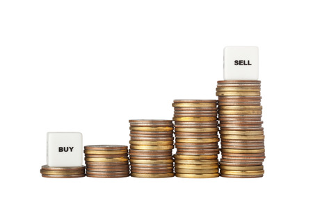 buy sell: Stacks of increasing amount of coins with Buy Low and Sell High signs isolated on white background Stock Photo