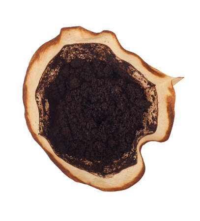 Used coffee grounds in a filter isolated on white background