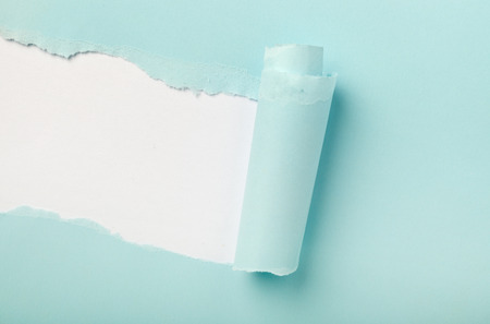 unveil: Tear in a piece of blue paper revealing white background underneath