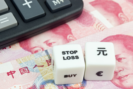 speculate: Chinese currency with calculator and dice showing STOP LOSS Stock Photo
