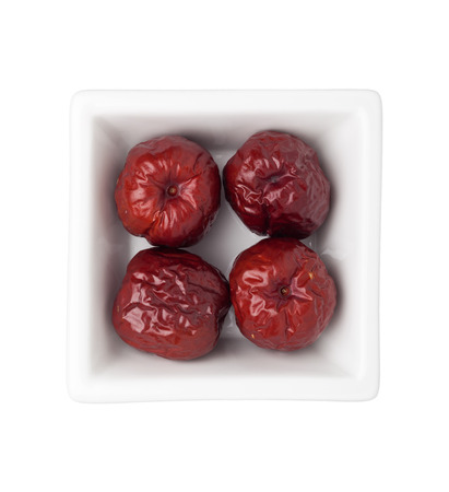 herbology: Dried big red jujubes in a square bowl isolated on white background Stock Photo