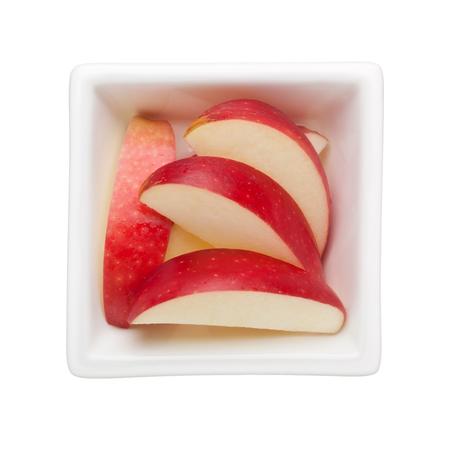 manzana roja: Rebanadas de manzana roja en un cuenco cuadrado aisladas sobre fondo blanco