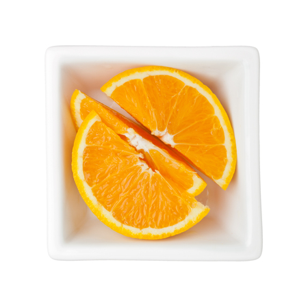 nutriment: Slices of orange in a square bowl isolated on white background