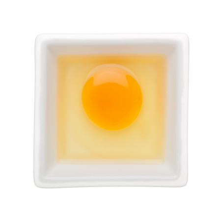 nutriment: Raw egg in a square bowl isolated on white background