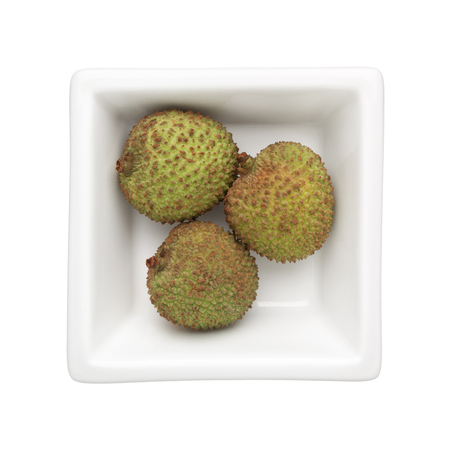 Green lychees in a square bowl isolated on white background Stock Photo