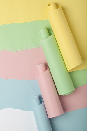 unveil: Tear in colored papers revealing white background underneath