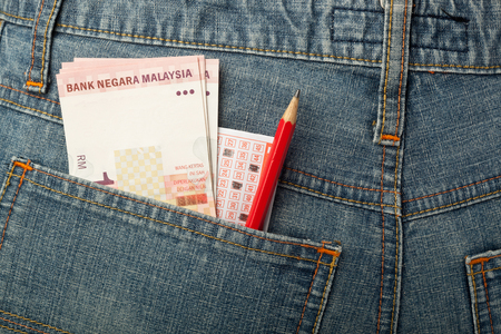 wager: Malaysian money and lottery betting slip in back pocket