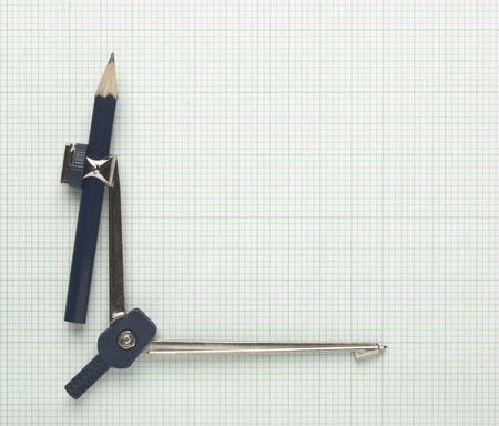 blank spaces: Compass forming the axis on graph paper Stock Photo