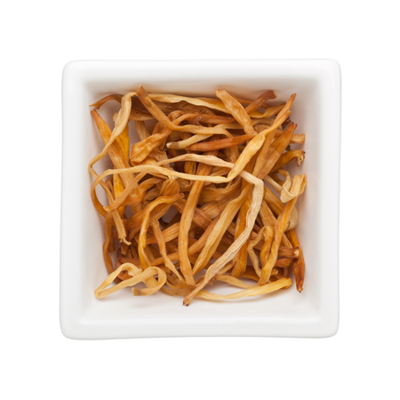 herbology: Traditional Chinese Medicine - Jin Zhen (dried daylilies) in a square bowl isolated on white background