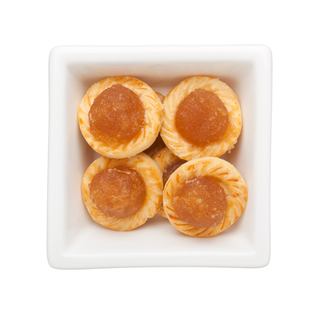 Pineapple tarts in a square bowl isolated on white background  Banco de Imagens