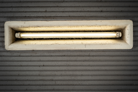 Dirty ceiling lighting with a neon tube at the subway landing stage, Hamburg, Germany.
