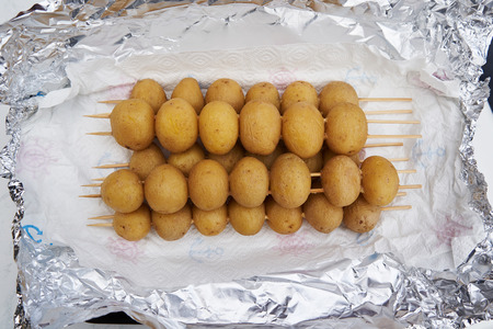 Fresh whole baby potatoes in their jackets threaded onto wooden skewers for grilling heaped on silver aluminium foil conceptual of a BBQ, picnic, braai or cookout Banco de Imagens