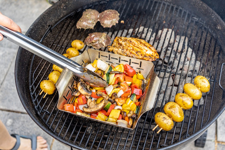 Vegetables, potato skewers and meat on a charcoal grill, terrace, hand and foot.