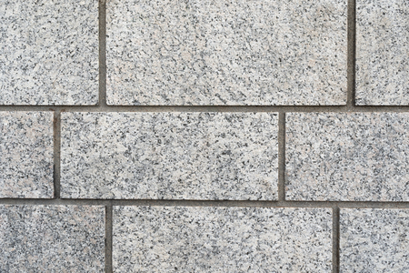 Background texture of a grey granite rectangular brick wall with neat grouting in a full frame view Banco de Imagens