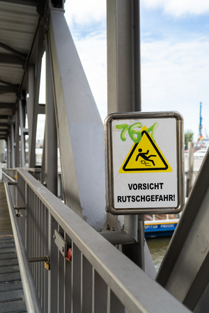 Warning sign on a pedestrian bridge not to Slip and Fall with scrawled green graffiti lettering