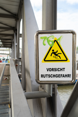 Sign on a bridge warning against slipping and falling with green scrawled graffiti in a close up view