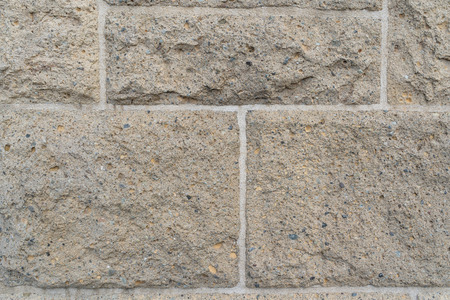 Close up on rough rectangular stone bricks of different sizes in wall connected by bright white grout