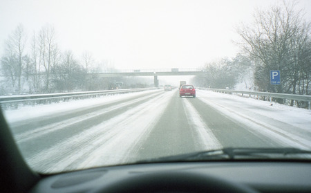 Snowy highway road and bad weather conditions viewed from drivers point of view, through the windshield of moving car. Overpass bridge is visible ahead.