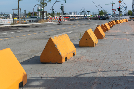 Long receding line of anti-terror barricades in the form of large concrete triangular blocks along an urban street to protect pedestrians from vehicle attacks. Banco de Imagens