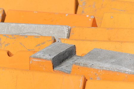 Orange and concrete barriers to prevent vehicular terrorism used to line a street in a close up full frame view. Banco de Imagens
