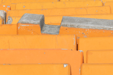 Close up detail of orange concrete road barriers used to line streets protecting pedestrians from terrorist attack using motor vehicles. Banco de Imagens
