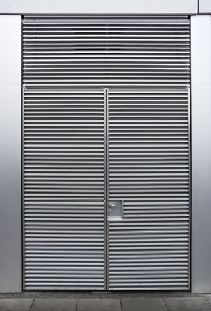 Closed metallic grey double door with horizontal ripples, viewed from outside the building. Full frame background concept. Imagens