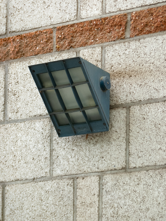 Wall-mounted black metal spotlight for security and illumination on an old stone block wall in a Botanical Garden.