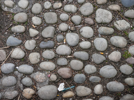 Old worn round cobblestones set into the ground on a walkway with scattered discarded cigarette butts in a full frame background texture viewed from above.